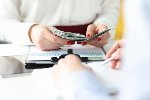 女性の手は仕事のテーブルで現金を数えています