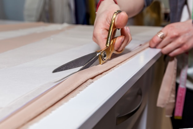 흰 탁자 위에 있는 종이 패턴에 여성의 손이 재단사의 가위로 천을 자르고 있다