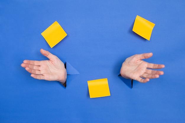 Женские руки разведены на синем фоне. женские вставлены в бумажный фон, сверху три бумажные палочки. место для надписи.