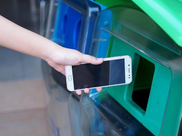 여성의 손이 오래된 휴대 전화를 쓰레기통에 버리고 있습니다.