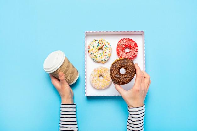 Женские руки держат пончик и чашка кофе на синем. концепт кондитерский магазин, выпечка, кофейня.