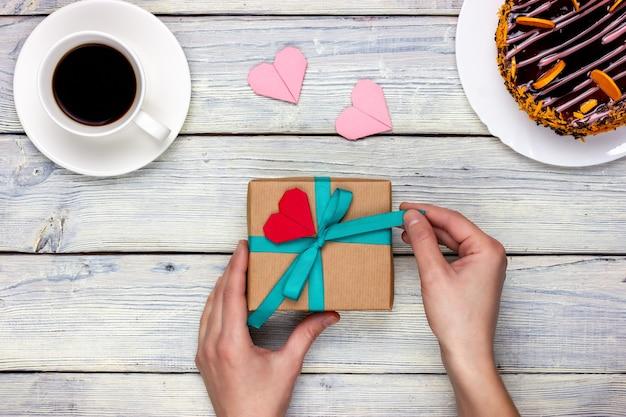 여성의 손에 심장의 형태로 메모와 함께 선물을 들고 있습니다. 위에서 봅니다.