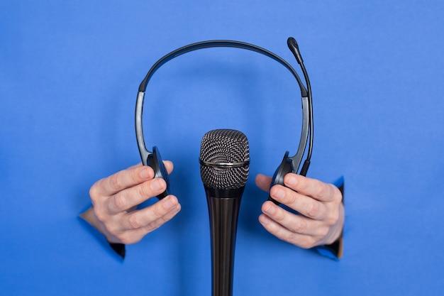 Женские руки держат микрофон и наушники на синем фоне. женские вставлены в бумажный фон. место для надписи.