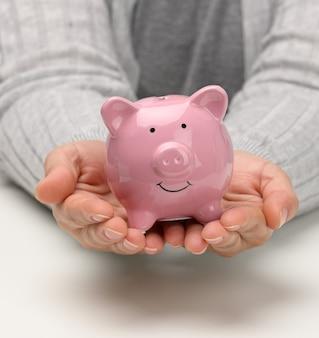 女性の手はピンクのセラミック貯金箱を持っています。蓄積の概念、予算管理