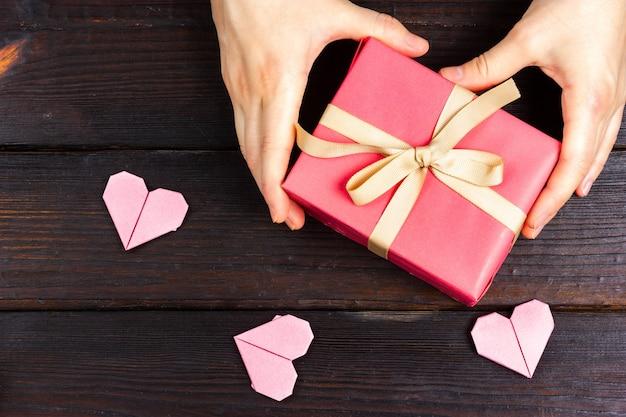 여성의 손에 어두운 나무 테이블에 분홍색 선물을 들고있다.