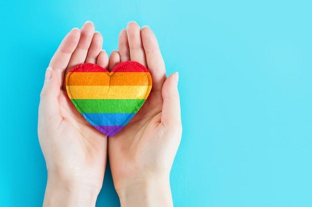 女性の手は、青色の背景にlgbtコミュニティの虹のハートマークを保持しています。ポスター、チラシ、バナー、コピースペースのlgbtの背景。 lgbtフラグに描かれた心