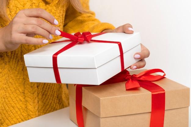 女性の手は、クリスマス、新年の赤い弓で工芸品と白いギフトボックスを保持しています。孤立したコピースペース。顔のない居心地の良い暖かい黄色のセーターを着た女性。