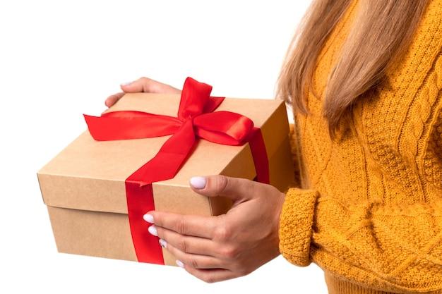 女性の手は、クリスマス、新年の赤い弓でクラフトギフトボックスを保持しています。孤立したコピースペース。顔のない居心地の良い暖かい黄色のセーターを着た女性。