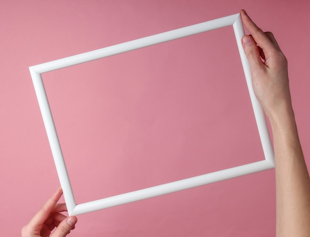 여성의 손에 핑크 파스텔 표면에 복사 공간에 대 한 빈 흰색 프레임을 잡고있다