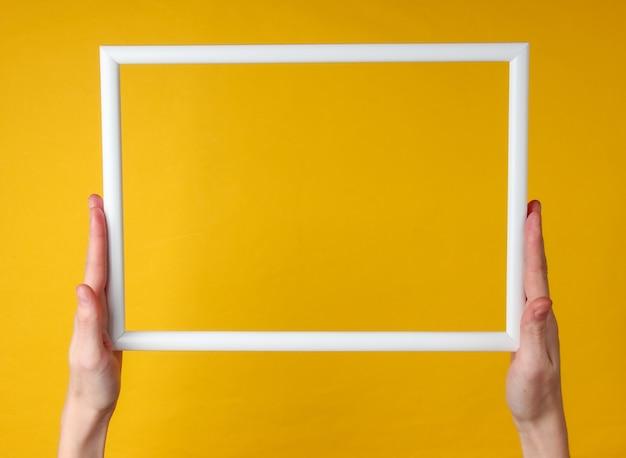 女性の手は黄色の表面のコピースペースのために空の白いフレームを保持しています