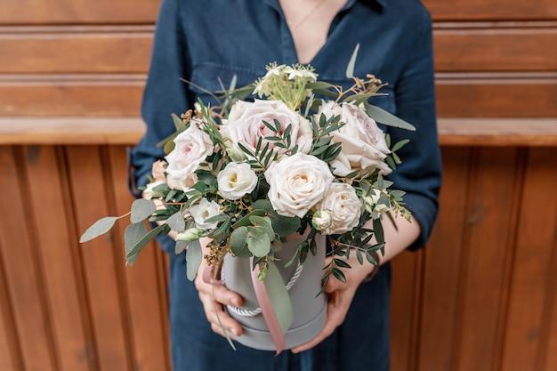 Женские руки держат цветочную коробку. концепция праздников и поздравлений с днем рождения.