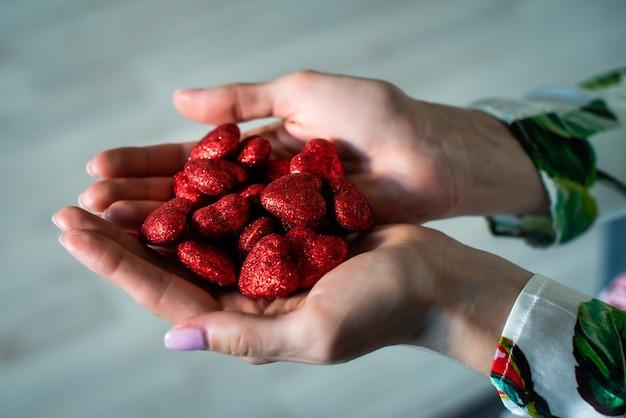 여성의 손은 많은 빨간색 빛나는 마음을 잡고 있습니다. 발렌타인 데이. 사랑, 2월 14일. 사랑, 신뢰, 믿음, 도움의 개념.