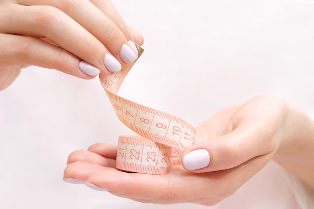 Female hands are holding a measuring tape. slim body and diet concept