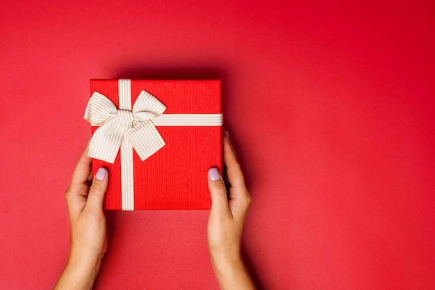 Female hands are holding present box or gift box with gold ribbon over red