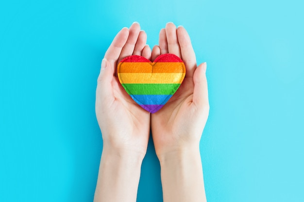 Female hands are holding a rainbow heart symbol of the lgbt community on a blue background, greeting card, background for poster, flyer, banner, copy space. lgbt day concept. lgbt background.