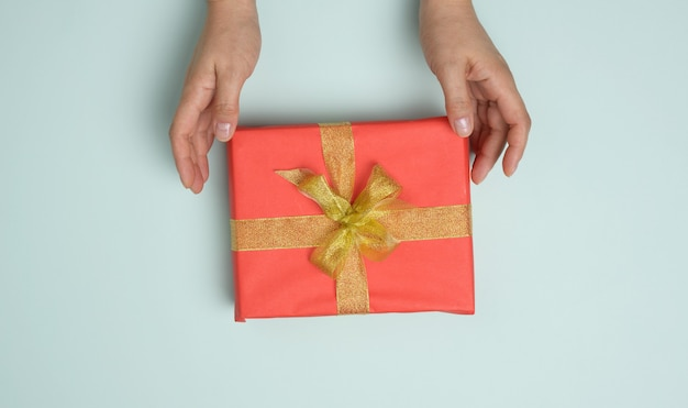 Female hands are holding red gift box on a blue background, concept of congratulations
