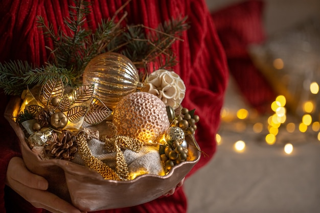Female hands are holding a set of christmas decorations. the concept of a cozy home and a festive atmosphere.