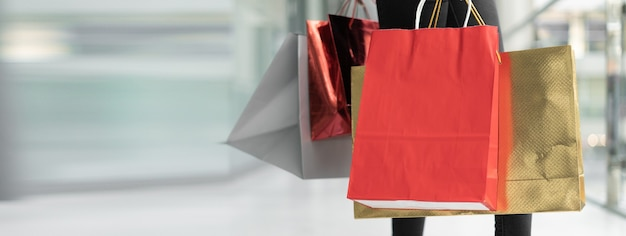 Female hands are holding several colored packages. shopping mall concept. baner. copy space.