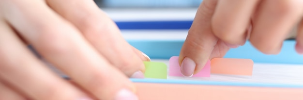 Female hands are looking for document among many papers with colorful stickers paperwork
