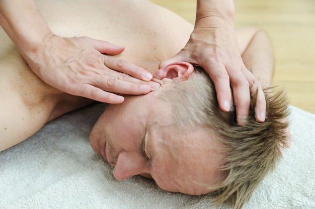 Female hands are massaging the man's ear after acupuncture