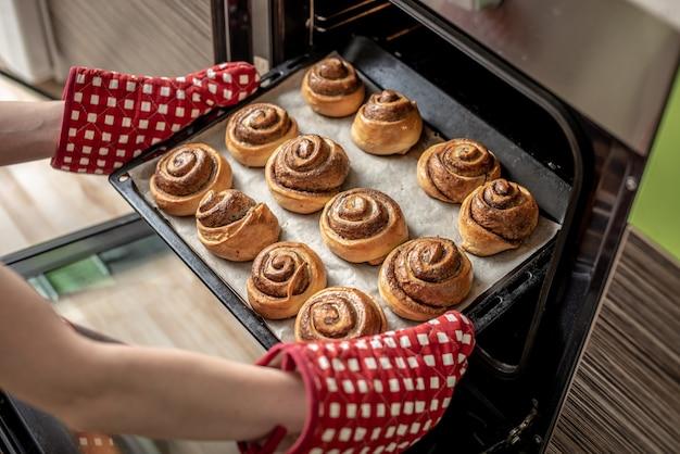 Женские руки достают свежие ароматные булочки с корицей из горячей духовки