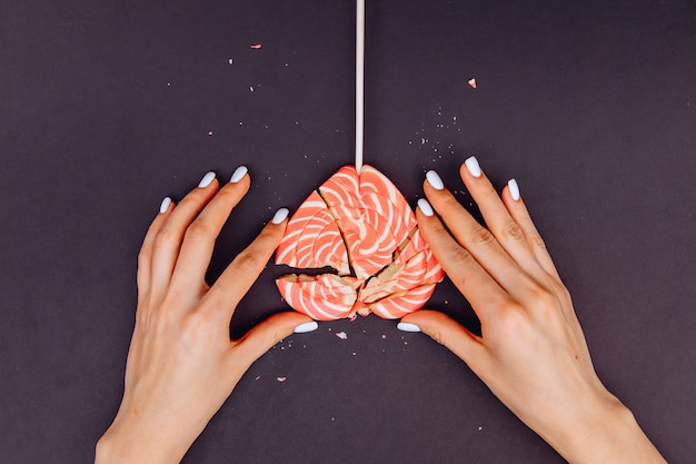 Female hands are trying to collect broken candy in the form of a heart,  black background.