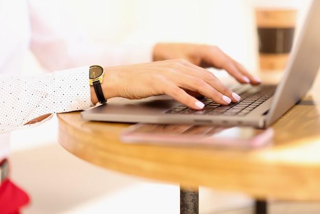 ノートパソコンのキーボードのクローズアップで女性の手が入力しています。