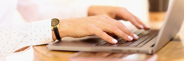 女性の手がノートパソコンのキーボードのクローズアップで入力しています