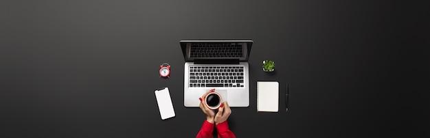 여성의 손은 당신의 비문을 위한 장소가 있는 현대적인 노트북 블랙 테이블에서 일하고 있습니다