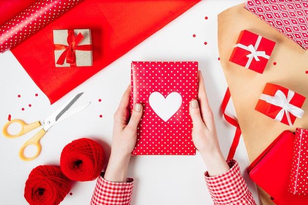 여성 손이 빨간색 흰색 테이블에 발렌타인 선물을 포장하고 있습니다