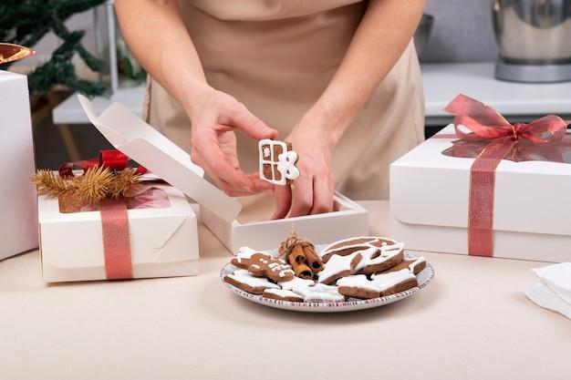 女性の手がジンジャーブレッドのクッキーをギフトボックスに包んでいます。クリスマスボックス。閉じる。
