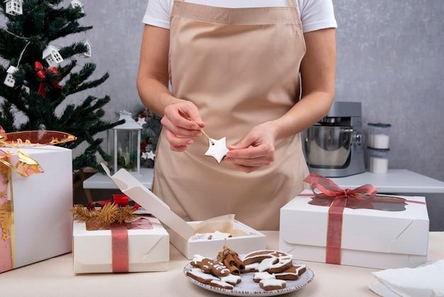 여성의 손이 선물 상자에 진저브레드 별을 포장하고 있습니다. 크리스마스 상자입니다. 확대.