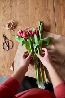 Женские руки, аранжировка розовых тюльпанов на деревянном столе, флористическое хобби на рабочем месте, бизнес, diy, концепция весеннего подарка, сверху.