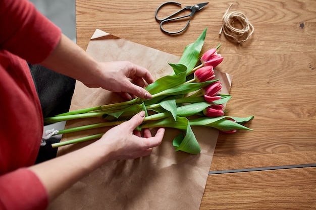 Female hands arranging pink tulips bouquet on wooden table, floristic hobby workplace , business, diy, spring gift concept, from above.