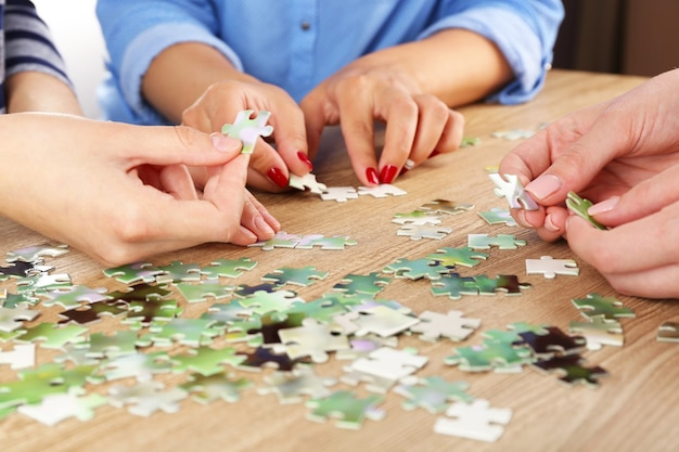 木製のテーブル、クローズアップでパズルを組み立てる女性の手