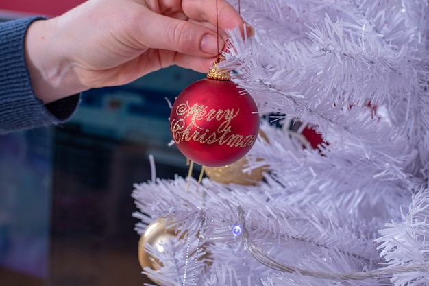 Female hands attaching red christmas decoration on to white christmas tree.