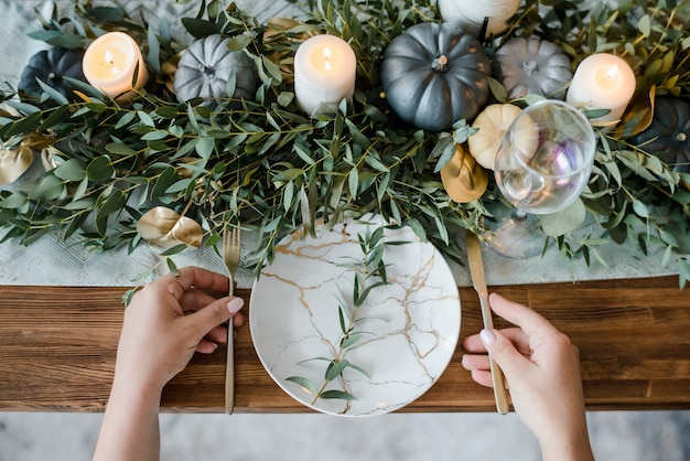 Female hands above autumn table setting with pumpkins. halloween or thanksgiving spooky tableware on dark wooden background
