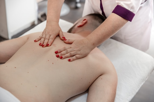 Female hands do a back massage to a man in the salon.