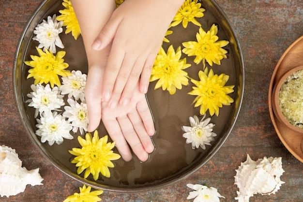 Mani femminili e ciotola di acqua termale con fiori, primi piani. mani spa.