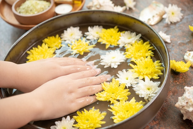 Female hands and bowl of spa water with flowers, close up. hands spa.