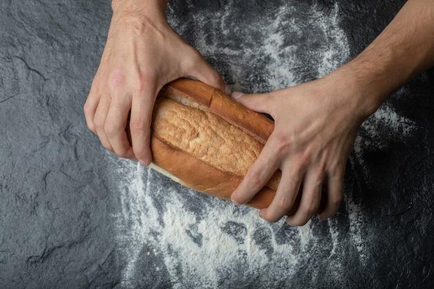 焼きたてのパンを壊す女性の手、クローズアップ。