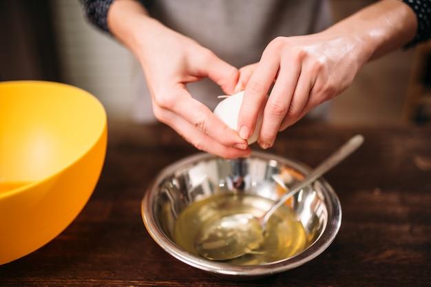 Женские руки разбивают яйцо в миску на деревянном столе. приготовление вкусного торта.