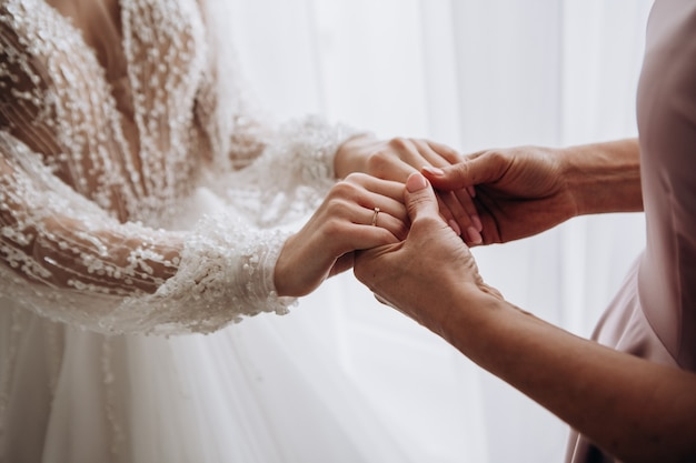 Female hands of bride and mother on wedding day inside home