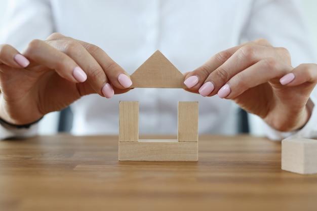 Женские руки строят дом из деревянных кубиков