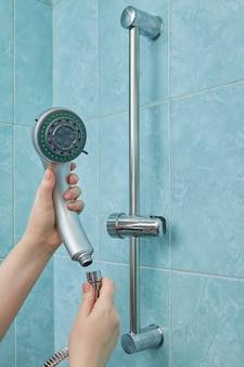 여성의 손은 파란색 벽이있는 욕실에서 샤워 헤드를 새 것으로 변경합니다.
