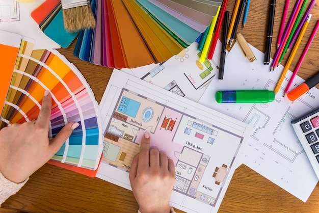Женские руки выбирают цвет стен спальни