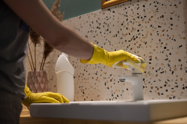 Female hands cleaning bathroom washing the washbasin in protective gloves at home