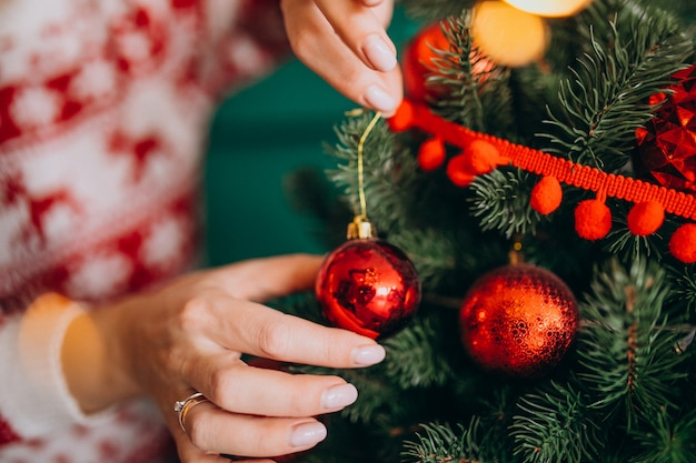 Female hands close up, decorating christmas tree with red balls