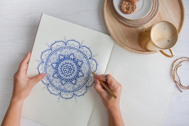 女性の手をクローズアップ描画装飾的な丸い花曼荼羅。趣味とリラクゼーション。木製トレイ上のコーヒーとクッキーのマグカップ。白色の背景。