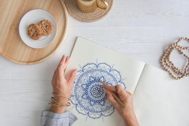 女性の手をクローズアップ描画装飾的な丸い花曼荼羅。趣味とリラクゼーション。木製トレイ上のコーヒーとクッキーのマグカップ。白色の背景。 Premium写真